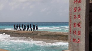 Soldiers of China's People's Liberation Army (PLA) Navy patrol near a sign in the disputed Spratly Islands.