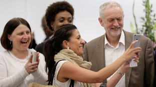 Jeremy Corbyn stops to have a photo taken with supporters.