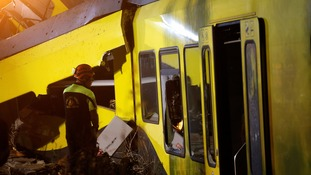 A rescuer works at the site where two passenger trains collided near Bari, Italy.