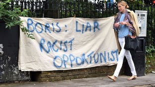 A woman walks past a banner put up by protesters opposite the home of Boris Johnson in north London.