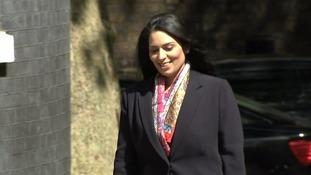 Priti Patel smiles on her way into Downing Street