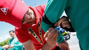 A man ties a black armband on a Tour de France steward.