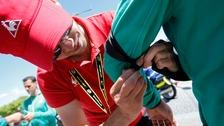 A man ties a black armband on a Tour de France steward.