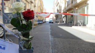 Roses are placed at a barricade near the scene in Nice