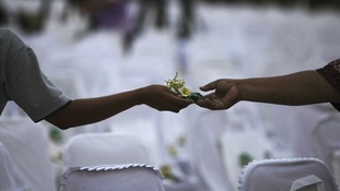Flower exchanged between friends during a commemoration service for the 10th anniversary of the Bali bombing