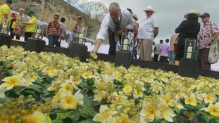 A man lays a flower at a pond commemorating the victims of the 2002 attacks