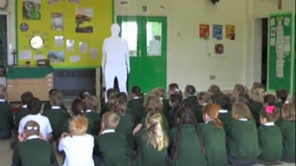 Children in assembly gaze up at the cardboard clergyman.
