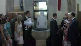 A congregation in church looking at a cardboard cut-out of a clergyman.