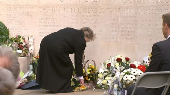 A woman lays a wreath of flowers by the memorial in St James's Park.