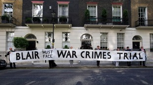 Protesters hold a banner in London before the report was published.