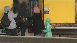 Refugees climb into a lorry