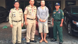 Midgley with Cambodian police officers following his arrest in Siem Reap