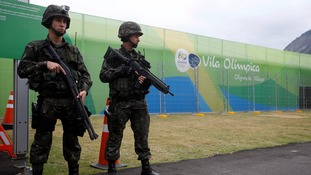 Soldiers stand guard outside the Olympic village in Rio