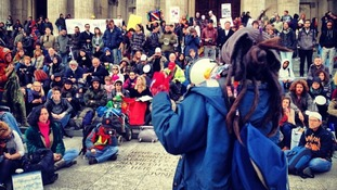 A performance poet speaks to demonstrators outside St. Paul's Cathedral