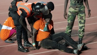 Security officials assist an injured fan.