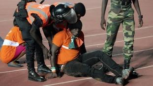 Security officials assist an injured fan.