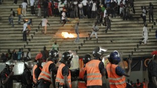 Senegalese football fans throw rocks at police.