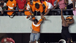 Fans of Ivory Coast's national football team help other fans escape the violence in the Leopold Sedar Senghor stadium in Dakar.