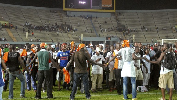 Fans of Ivory Coast&#x27;s national football team help other fans escape the violence in the Leopold Sedar Senghor stadium in Dakar.