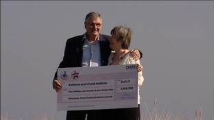 Couple pose with their giant cheque