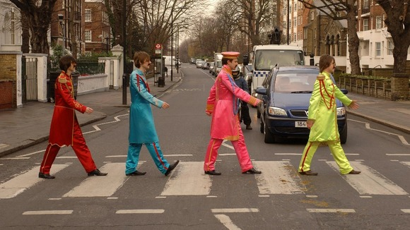 Beatles look-a-likes cross the famous zebra crossing in Abbey Road, St John's Wood.