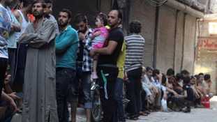 People queue for bread in rebel-held Aleppo