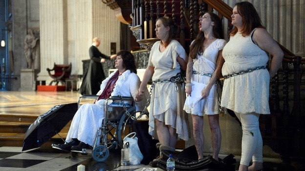 Female activists from the Occupy movement stage a protest by chaining themselves to the pulpit in St. Paul's Cathedral.