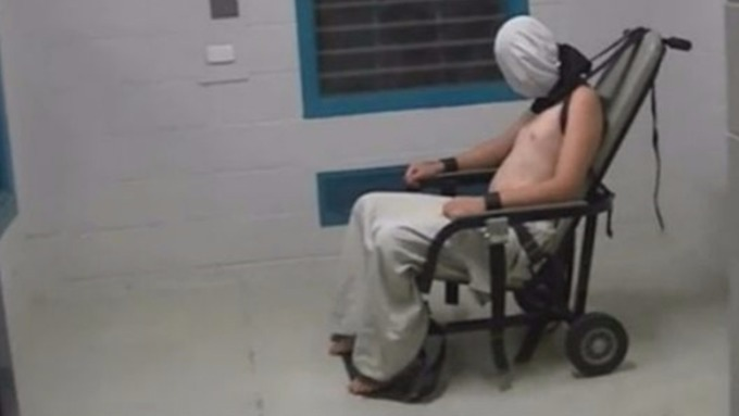 A 17-year-old boy is hooded and shackled to a chair in the footage.