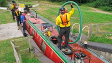 Specialist rescue crews work on a narrow boat which sank while passing through a lock along the Droitwich Junction Canal.