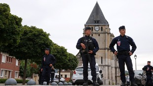 Police near the church in Saint-Etienne-du-Rouvra where the priest died.