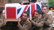 The coffin of Corporal Hoole is carried through the crowd