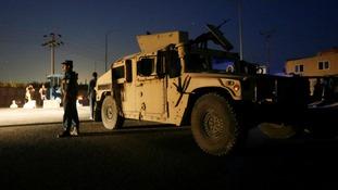 Afghan policemen keep watch near the site of the blast
