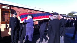 Rail engineers carry the coffin onto the train