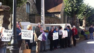 Campaigners demonstrate outside memorial