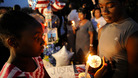 A teenager lights a candle during a vigil for Trayvon Martin in Sanford