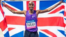 Mo Farah celebrates with the union flag after winning the Men's 3000m race during the Glasgow Indoor Grand Prix at the Emirates Arena