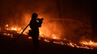 A firefighter sprays water on the flames.