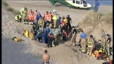Emergency services try to hold back sand