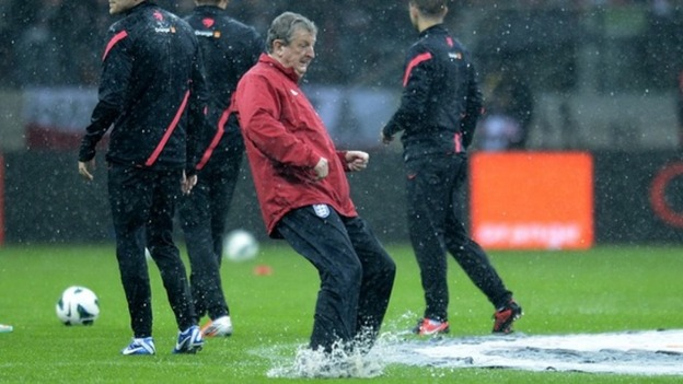England boss Roy Hodgson tests the waterlogged pitch