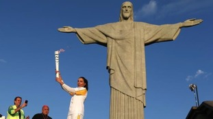 The Olympic torch was raised next to Rio de Janeiro's most famous statue.