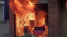 A smashed window and flames at a shop in Market Street in Manchester city centre