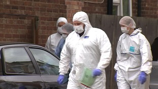 Police in protective clothing arrive at the house