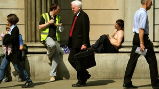 Workers enjoy the lunchtime sunshine outside the Bank of England, London.
