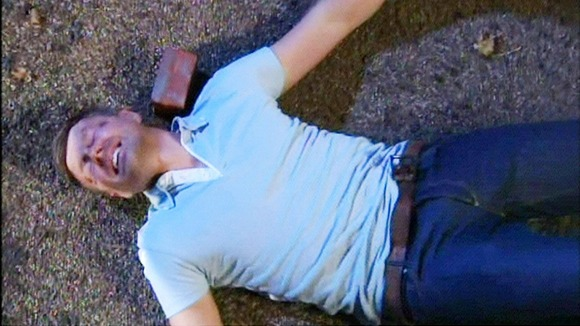 Carl King played by Tom Lister , lies on the floor after being hit with a brick by Chastity Dingle