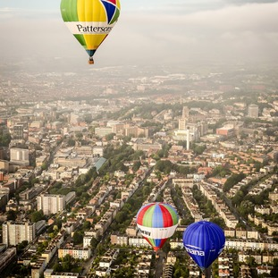 Hot air balloons pass over the city of Bristol during a mass balloon launch from Clifton Downs