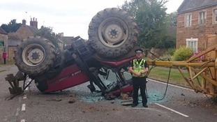 Dramatic scene: a police officer poses with the tractor