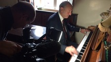 Frank plays the piano to keep the punters entertained