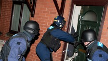 Police officers smash into a North Manchester property during drugs raids.