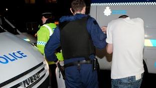 Police lead man away during dawn raids.