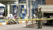 A Police Explosive Ordnance Disposal official inspects the site of a bomb blast in Hua Hin.
